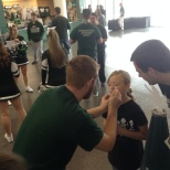 Ryan Young paints a young fan's face at the men's basketball game