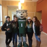 Baxter poses with the Cheercats on Green Day Friday